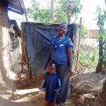 The Water Project : 13-kenya4732-claire-poses-with-her-son-next-to-her-bathroom