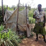 The Water Project: Shikoti Community, Amboka Spring -  Mrs Egesa Beside Her Latrine