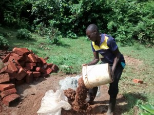The Water Project:  Community Member Helps With Cement Work