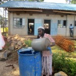 The Water Project: Bumuyange Secondary School -  Parent Fetches Construction Water