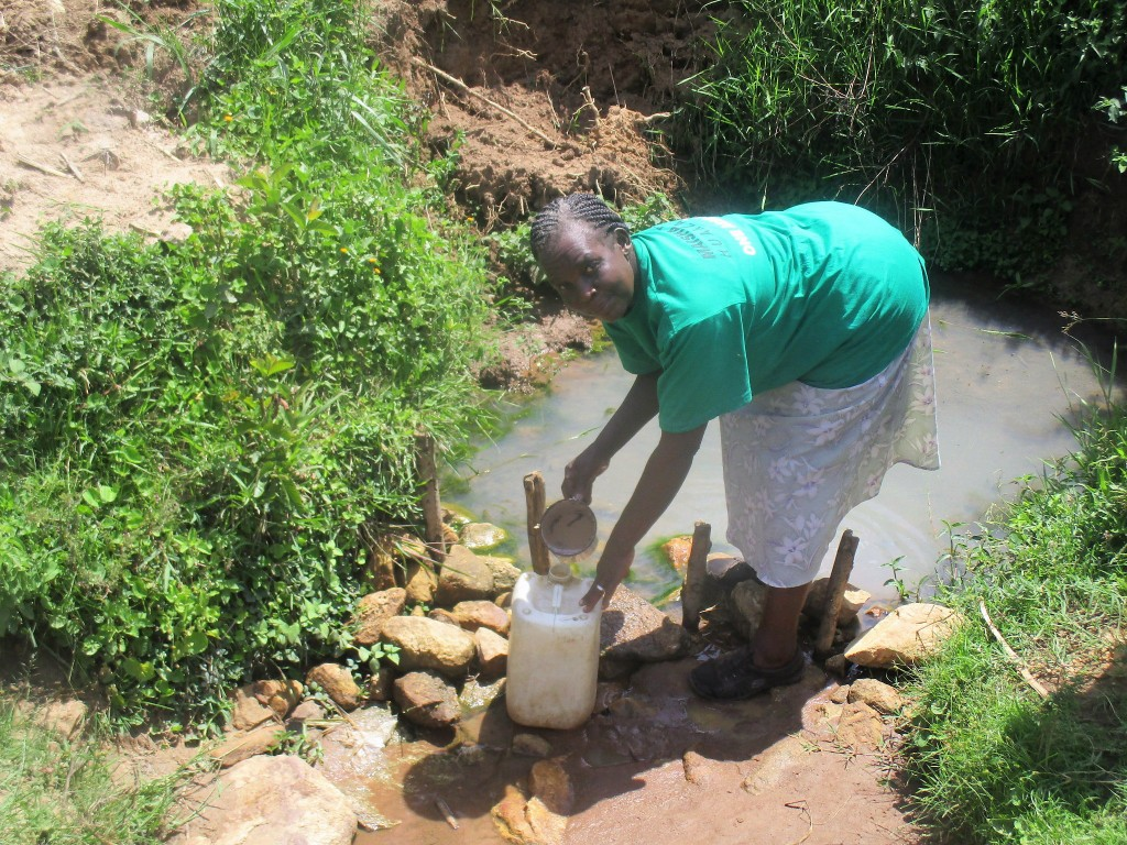 The Water Project : 2-kenya4755-mrs-fanice-fills-her-water-jugs-at-the-puddle