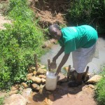 The Water Project: Mulundu Community -  Mrs Fanice Fills Her Water Jugs At The Puddle