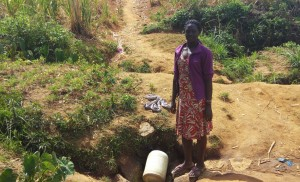 The Water Project : 4-kenya4729-lady-waits-for-her-jerrycan-to-fill
