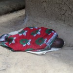 The Water Project: Mulundu Community -  A Kid Ailing From Malaria Sleeping Outside Her House With No Medical Attention