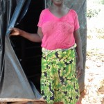 The Water Project: Igogwa Community -  Mrs Jane Proud Of Her Improvised Latrine