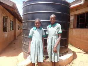 The Water Project:  Girls Next To The Liter Tank