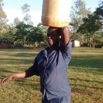 The Water Project: Iyenga Primary School -  School Cook Carrying Container From Spring