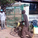 The Water Project: Eshisuru Primary School -  Community Member Coming To Fetch Water