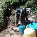 The Water Project: Handidi Community, Matunda Spring -  Zablon Fetching Water At Matunda Spring