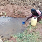 The Water Project: Simuli Community, Lihala Sifoto Spring -  Mrs Lihala Fetching Water