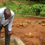 The Water Project: Mutambi Community, Kivumbi Spring -  Community Member Watches Pipe Installation