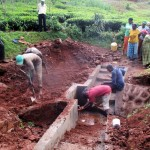 The Water Project: Mutambi Community, Kivumbi Spring -  Community Members Watch Final Stages