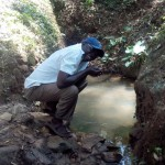 The Water Project: Elunyu Community, Saina Spring -  Mr Erastus Chimwadi Drinking Water From The Spring