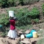 The Water Project: Handidi Community, Matunda Spring -  Woman Lifts A Container Full Of Water