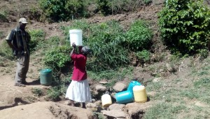 The Water Project:  Woman Lifts A Container Full Of Water