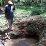 The Water Project: Mkunzulu Community, Museywa Spring -  Mr Shadrack Muuchi Showing Us The Spring