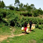 The Water Project: Kakubudu Community, Fred Lagueni Spring -  Women Going To Fetch Water
