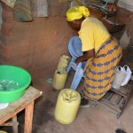 The Water Project: Kaani Community E -  Justina Pius Gathering Her Water Containers