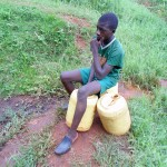 The Water Project: Lugango Community, Lugango Spring -  Michael Sits On His Containers Waiting For Water To Settle