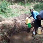 The Water Project: Mkunzulu Community, Museywa Spring -  Fetching Water