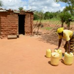 The Water Project: Kaani Community E -  Justina Pius And Her Jerrycans