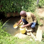 The Water Project: Kakubudu Community, Fred Lagueni Spring -  Village Elder Fetching Water