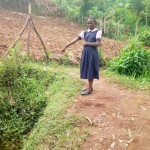 The Water Project: Musudzu Primary School -  Student Points At Dirty Water Source She Uses