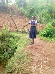 The Water Project:  Student Points At Dirty Water Source She Uses