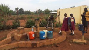 The Water Project:  Primary Students Wait For Community Member To Finish At Well