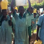 The Water Project: Eshilakwe Primary School -  Carrying Heavy Water Containers Back To School