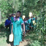 The Water Project: Chandolo Primary School -  Carrying Water Back To School