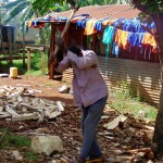 The Water Project: Ebubayi Secondary School -  Groundsman Splitting Wood In Front Of Clothes Drying On Roof