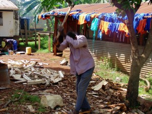 The Water Project:  Groundsman Splitting Wood In Front Of Clothes Drying On Roof