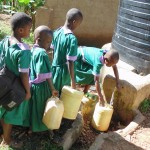 The Water Project: Chandolo Primary School -  Pupils In Line To Get Water From Plastic Tank