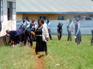 The Water Project:  Principal Leading Her Students To Pick Up Litter