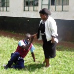 The Water Project: Ebubayi Secondary School -  Principal Helps A Sick Boy Up Off The Ground