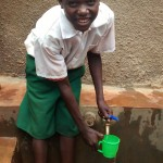 The Water Project: Emurembe Primary School -  Austine Makata Enjoying The Fresh Water From The Tank