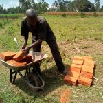 The Water Project: Mukhuyu Community, Shikhanga Spring -  Man Delivering Bricks