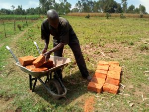 The Water Project:  Man Delivering Bricks