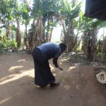 The Water Project: Emusanda Community A -  Woman Cleaning Her Compound