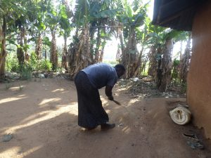 The Water Project:  Woman Cleaning Her Compound