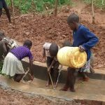 The Water Project: Ebuhando Community -  Children Cleaning The Spring