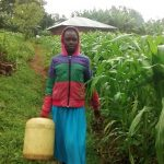The Water Project: Lwenya Community, Warosi Spring -  Carrying Water