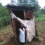 The Water Project: Mwichina Community -  A Girl Stands By Her Latrine