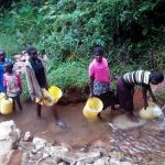 The Water Project: Shilakaya Community, Shanamwevo Spring -  Community Members Fetching Water