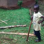 The Water Project: Chandolo Community -  Girl Splitting Firewood