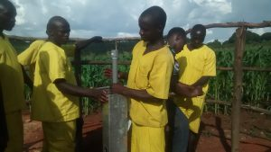 The Water Project:  Prisoners Helping With Pump Installation