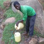 The Water Project: Chandolo Community -  Joseph Fetching Water