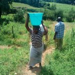 The Water Project: Ikonyero Community, Jesse Spring -  Lady Carrying An Open Bucket Of Water