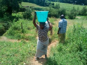 The Water Project:  Lady Carrying An Open Bucket Of Water